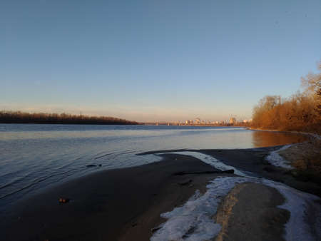 Winter - spring panorama of the river with reflections in the water. Partially melted snow, and reddish treetops lit by the sun at sunset. Foto de archivo