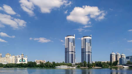 Panorama of Kiev with high-rise buildings and a church in the area of the Hydro park with reflection in the water, Dnieper river, Ukraine. Foto de archivo