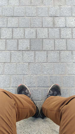 Legs of a seated man in shabby trousers and sneakers standing on a surface of paving slabs, top view, street, pedestrian zone.