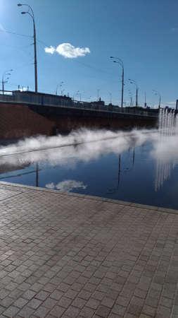 Fountain jets on background of blue sky with cloud. Sunlit pedestrian zone. Foto de archivo