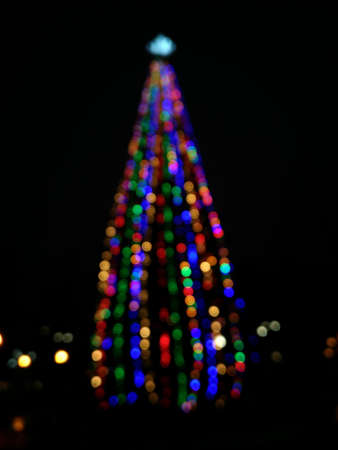 Christmas tree in defocus shooting at night in a city park, bokex reflexes, blurred image for background. Foto de archivo