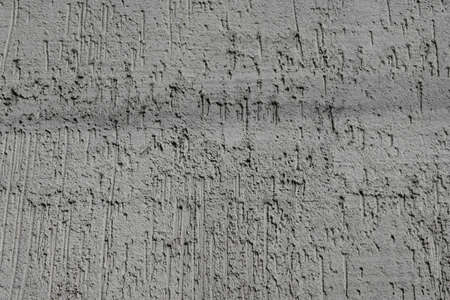 The texture of a decorative concrete wall, finishing the outer surface of the building from the street, the surface covered with grooves, recesses oriented vertically Foto de archivo