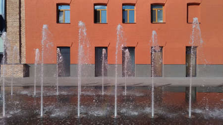Fountain jets on the background of a red brick building. Sunlit pedestrian zone.