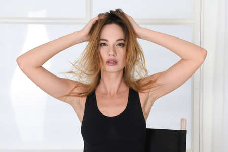 Woman with disheveled hair in a model pose, holds on to her head