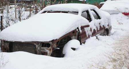 Altes gebrochenes Auto unter dem Schnee Standard-Bild - 69763118
