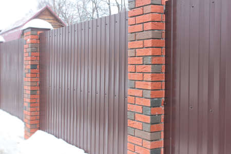 body dimensions: Metal fence with brick pillars in winter Stock Photo