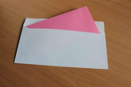 Ein Umschlag mit einer roten Karte auf einem Holztisch liegend Standard-Bild - 69930389