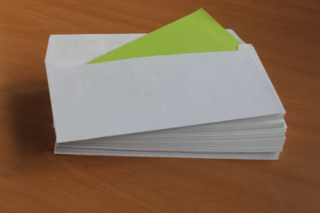 disorganized: White mailing envelope lying on a wooden table with a green card Stock Photo