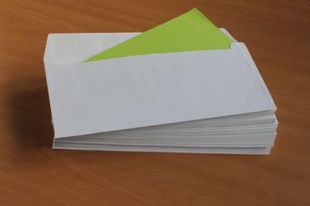 White Mailing Umschlag liegt auf einem Holztisch mit einer grünen Karte Standard-Bild - 69930395