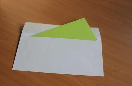 Ein Umschlag mit einer grünen Karte, auf einem Holztisch liegen Standard-Bild - 69930396