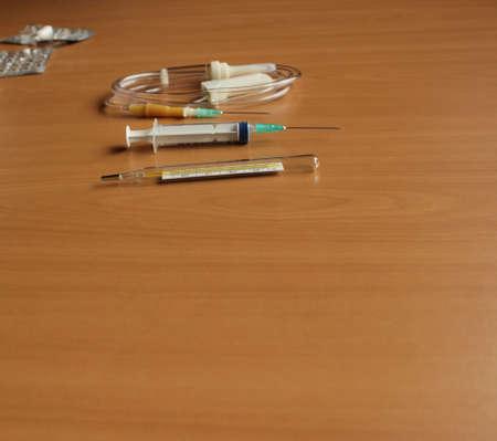 Medizinische Spritze und Tropfenzähler auf dem Tisch Standard-Bild - 71058708