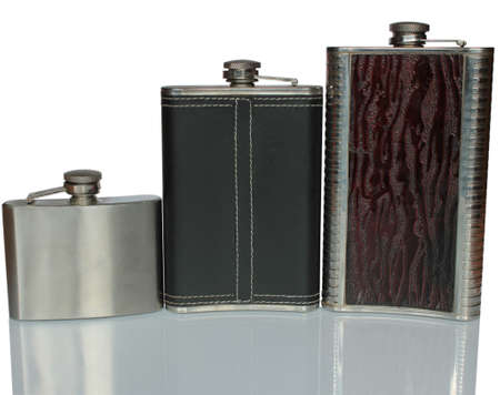 Three flat flask for alcohol on a glass table isolated on white