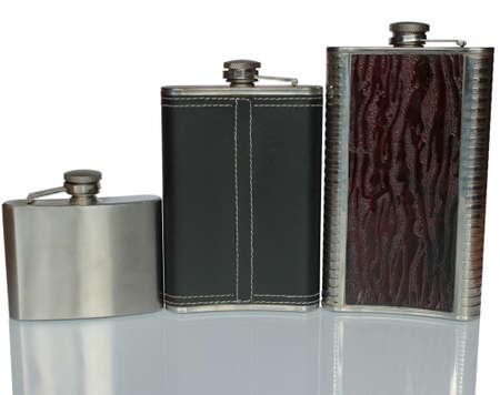 Drei flache Flasche für Alkohol auf einem Glastisch, isoliert auf weiss Standard-Bild - 74791187