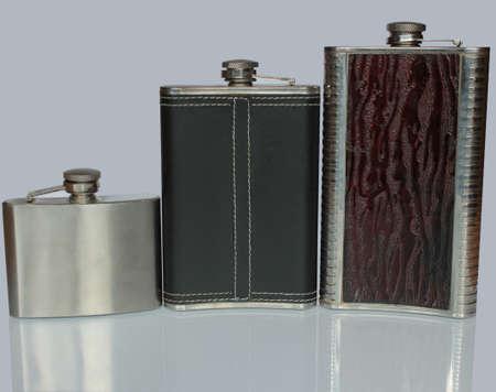 Flache Flasche drei für Alkohol auf einem Glastisch lokalisiert auf einem grauen Hintergrund Standard-Bild - 75723655