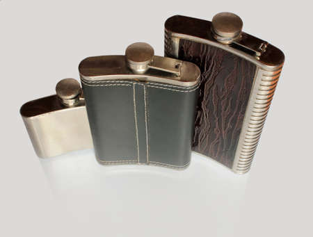 Three flat flask for alcohol on a glass table isolated on a gray background