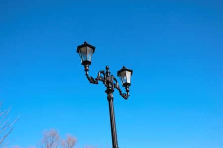 Alte Laterne auf Hintergrund des blauen Himmels, modernes Anreden, schwarzes Roheisen Standard-Bild - 75002209