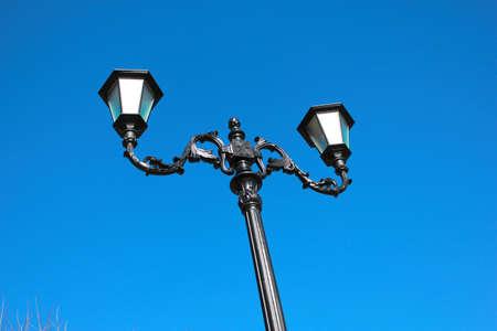 Alte Laterne auf Hintergrund des blauen Himmels, modernes Anreden, schwarzes Roheisen Standard-Bild - 75100877