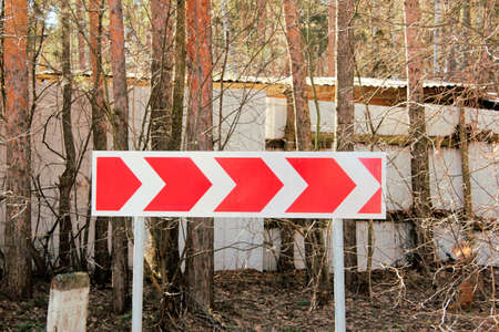 Gefährliche Biegung des Richtungsverkehrsschildes auf einem Hintergrund von Bäumen Standard-Bild - 75067339