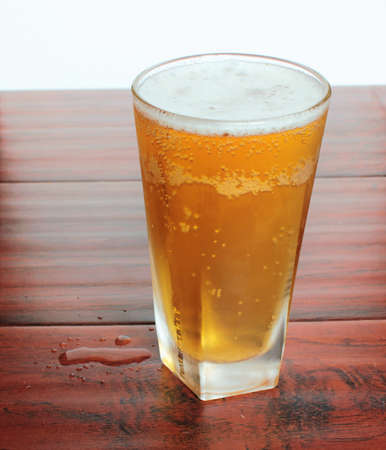 The misted glass of light beer on the table
