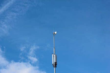 Handyturm gegen blauen Himmel mit Wolken Standard-Bild - 75743877