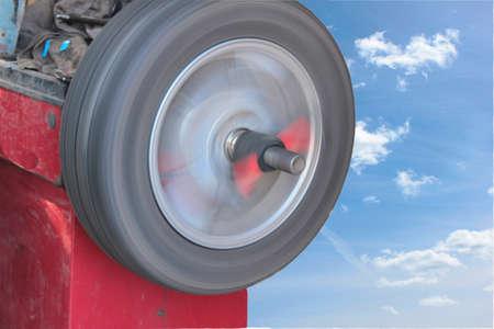 Das Rad dreht sich auf der Balanciermaschine auf dem Hintergrund des Himmels mit Wolken Standard-Bild - 75743878