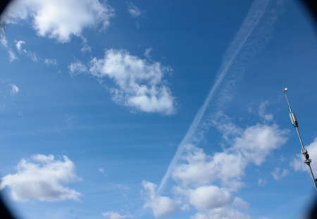 Bright blue sky with clouds and airplane contrail Standard-Bild