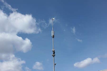 Handyturm gegen blauen Himmel mit Wolken Standard-Bild - 75743911