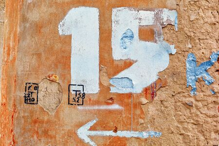 drawn number fifteen with an arrow on the old wall of the house