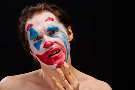 a young man smears clown makeup on his face with one hand, with bare shoulders, emotionally expresses feelings of mood, on a black background