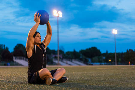 Athletic man using medicine ball during work out at night, Montreal, Quebec, Canada LANG_EVOIMAGES