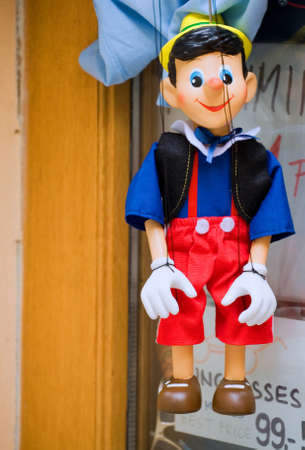 falsehood: Wooden marionette hanging in front of the shop - Pinocchio
