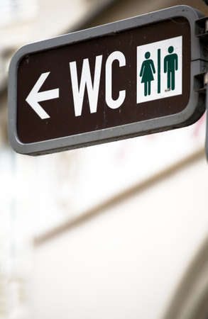 loo: Unisex toilet sign hinged on a post Stock Photo