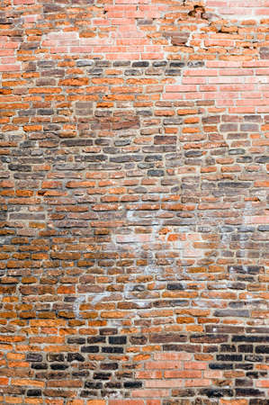 heavily: Photo of an old brick wall. The bricks are heavily textured and weathered.