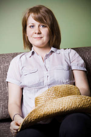 woman couch: Young woman sitting on a couch Stock Photo