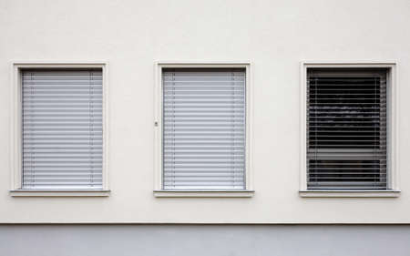 window shade: Three windows on a contemporary style building. Two of them have the blinds closed. Stock Photo