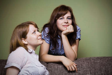 couch: Two young girlfriends sitting on a couch