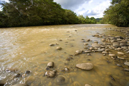 upstream: The Rio Coca in the Ecuadorian Amazon. The water brown with sediment because of deforestation upstream