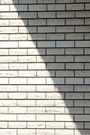 White brick wall with a shadow, background photo