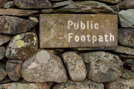 cumbria: Stone Public Footpath Sign.  The stone public footpath sign is embedded in a dry stone wall and is situated alongside Ullswater lake in the English Lake District. Stock Photo