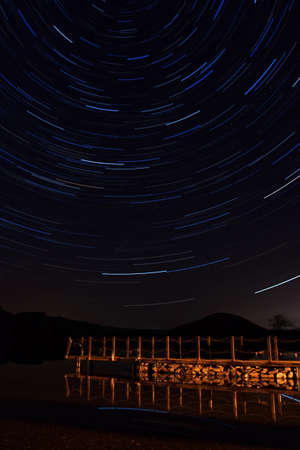 cumbria: Ullswater Star Trail.  Star trails above an Ullswater pier, a lake in the English Lake District.