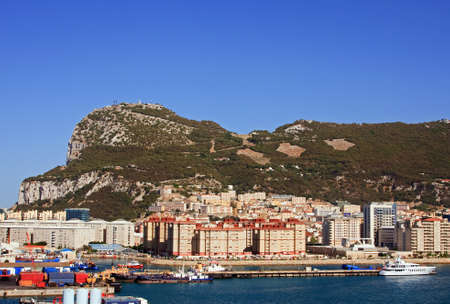 Gibraltar.  Gibraltar is a British territory located to the south of the Iberian peninsula at the entrance to the Mediterranean Sea.  The land is one of the most southerly points in Europe.