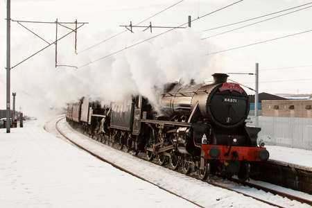 cumbria: The Winter Cumbrian Mountain Express.  Preserved steam locomotives 44871 and 45407 head the Winter Cumbrian Mountain Express north through Penrith station in Cumbria, on the west coast mainline. Editorial