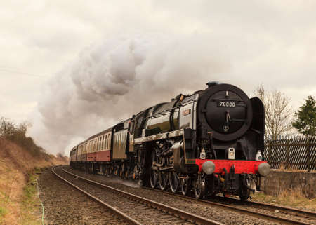 The Cumbrian Guardsman.  Preserved steam locomotive Britannia, heads the Cumbrian Guardsman into Langwathby station, on the Settle to Carlisle railway.