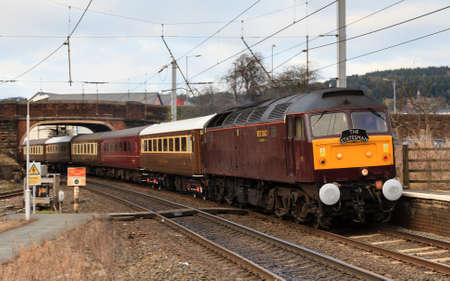 The Statesman.  A class 47 diesel locomotive heads the Statesman southbound through Penrith station in Cumbria, on the west coast mainline.
