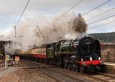 britannia: The Cumbrian Guardsman.  Preserved steam locomotive 70000 Britannia, heads the Cumbrian Guardsman southbound through Penrith station in Cumbria, on the west coast mainline.