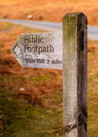 cumbria: Public Footpath Sign.  A wooden signpost marking a public footpath close to Crummock Water in the English Lake District national park. Stock Photo