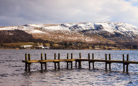 cumbria: Ullswater Pier.  A winter view across Ullswater to the snow capped hills in the English Lake District National Park.