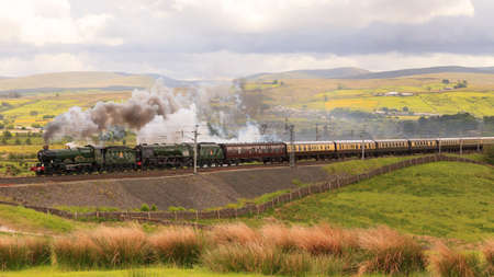 Der Cumbrian Eroberer. Konservierte Dampflokomotiven 5043 Earl of Mount Edgcumbe und 46233 Herzogin von Sutherland führen den Cumbrian Conqueror in Richtung Norden durch Tebay, Cumbria. Standard-Bild - 79363872