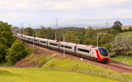 Virgin Pendolino.  A Virgin Pendolino heads north through Hackthorpe, Cumbria.  Virgin trains have operated the UK west coast main line rail franchise since 1987.