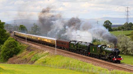 Der Cumbrian-Eroberer. Konservierte Dampflokomotiven 5043 Earl of Mount Edgcumbe und 46233 Herzogin von Sutherland Kopf der Cumbrian Conqueror durch Hackthorpe, Cumbria. Standard-Bild - 79363874